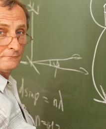 Scientist solves equation on blackboard